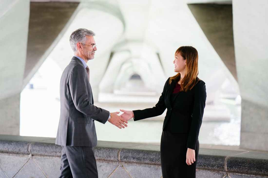 man and woman shaking hand in focus photography
